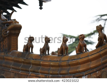 sculptures on the roof of ancient architecture in China. - stock photo