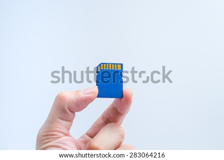 SD memory card with hand and finger hold isolate on white background. - stock photo