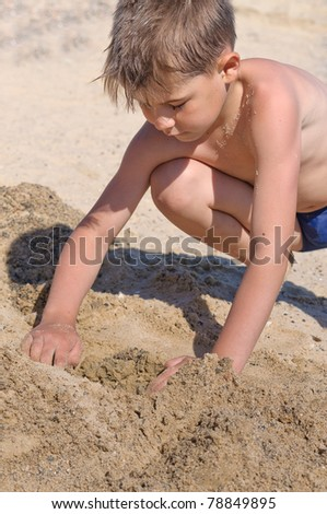 Sea, a boy in swimming trunks playing in the sand - stock photo