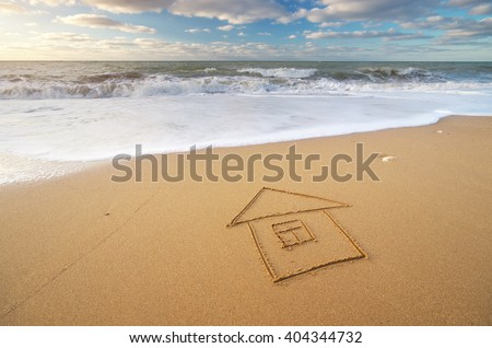 Sea and home on the sea sand. Nature and conceptual composition. - stock photo