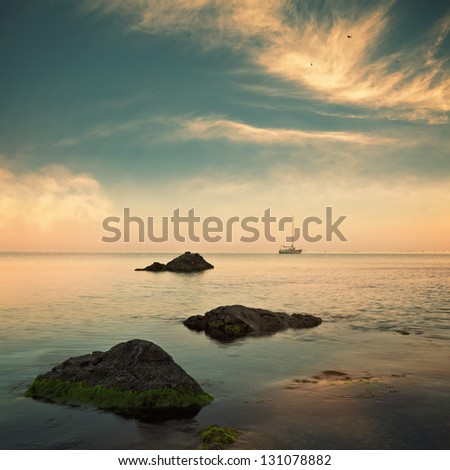 Sea and sailboat on horizon with cloudy sky. Retro style image colors
