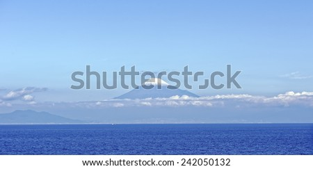 Sea approach to Shimizu, Japan with the sunlit snow capped peak of Mt. Fuji gleaming in the background - stock photo