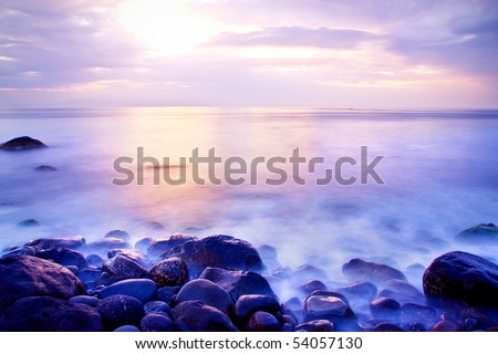 Sea at sunrise with motion waves due to a long exposure; rocks on foreground