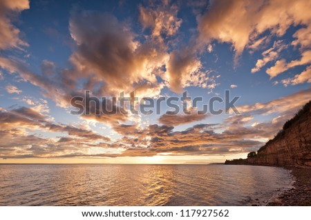 Sea at sunset with some motion blur water, the sky is in beautiful dramatic color - stock photo