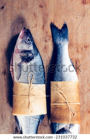 Sea bass fish raw on the wooden background - stock photo