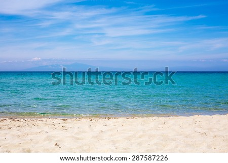 Sea, beach and blue cloudy sky. Mountains far away. Landscape background for design postcard and calendar