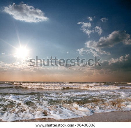 sea beach and blue sky with sun in storm - stock photo