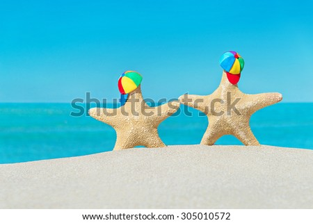 Sea beach traveling concept - two sea-stars in peaked caps walking at seashore against turquoise tropical ocean waves background - stock photo