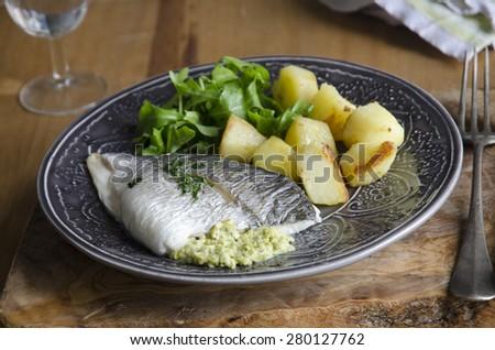 Sea bream stuffed with peas, broad beans and feta  - stock photo