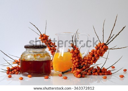 Sea buckthorn homemade jam in a jar, juice in a glass pitcher and fresh twig of sea-buckthorn with berries. Autumn still life and decoration with healthy fruits and products. - stock photo