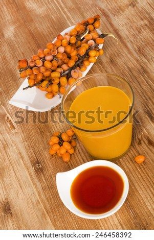 Sea buckthorn juice, oil and berries isolated on wooden background. Natural, healthy vitamin and detox. - stock photo