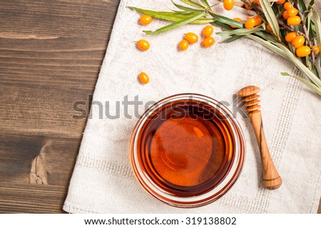 Sea buckthorn oil and branch with berries at right side top view - stock photo