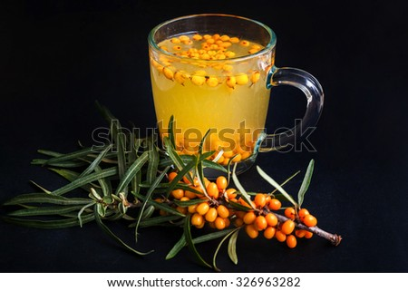 Sea buckthorn tea on dark background shallow DOF - stock photo