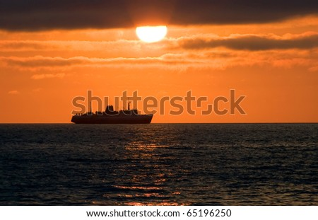 Sea cargo-passenger ferry on horizon during a decline (Pacific ocean) - stock photo