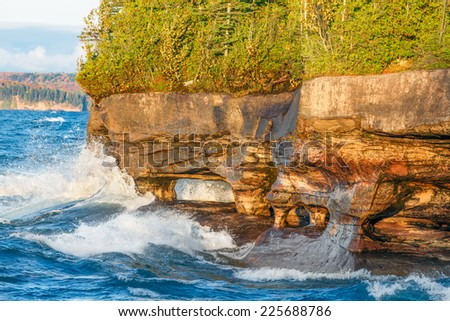Sea caves along the rocky, forested coastline  of Five Mile Point, near Christmas, Michigan, are pounded with waves near sunset. - stock photo