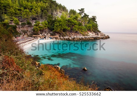 Sea coast of an island with beach and rocks while the sun is rising