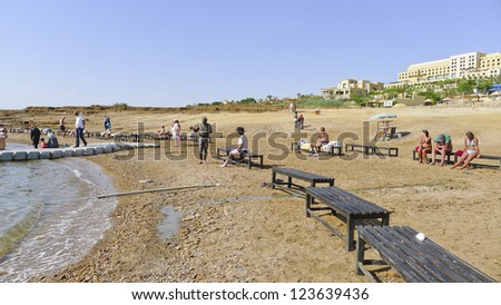 SEA DEAD - APR 20:  Unidentified tourists enjoying resort in  Sea Dead on April 20, 2012 in Jordan. The Dead Sea area, is famous for its health promoting environment for thousands of years. - stock photo