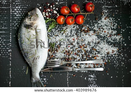 Sea fish with fragrant herbs, fresh vegetables, sea coarse salt and spices. Fresh sea fish. Sea fish. - stock photo