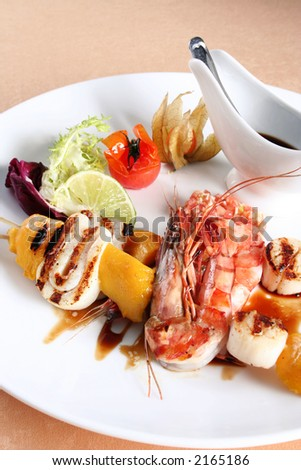 Sea food on grill detail with sauce and vegetable