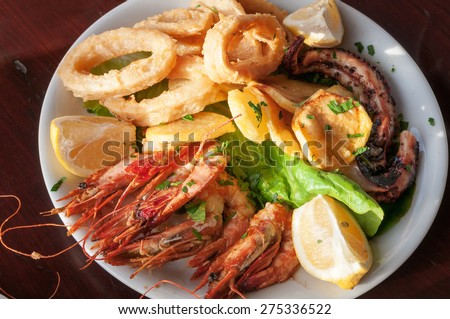 Sea food plate: squid rings, grilled prawns, octopus, lemon, salat - stock photo