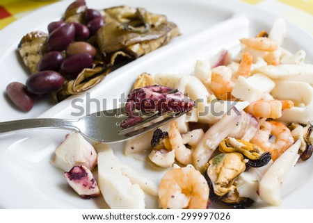 Sea food salad on the white dish with fork picking up the squid.  - stock photo