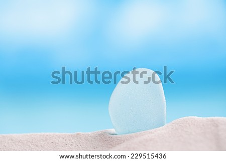 sea glass seaglass with ocean , white sandy beach and seascape, shallow dof - stock photo