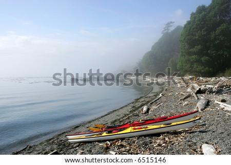 Sea kayaks on deserted ocean beach, San Juan Islands, Washington - stock photo