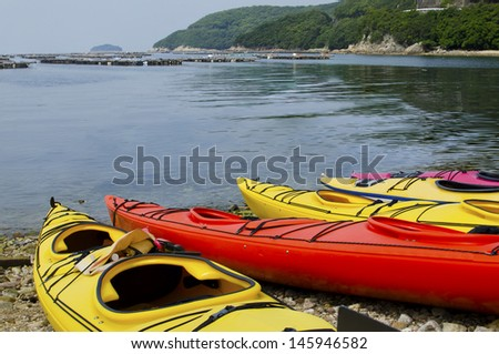 Sea kayaks ready and waiting on the beach for the next adventure on the ocean. - stock photo