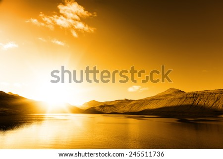 Sea landscape, vivid sunset. Calm sea. Cliffs on the horizon. Faroe Islands.
