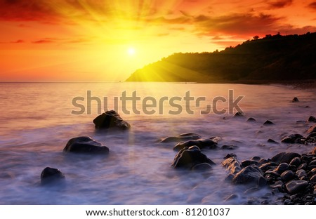 Sea landscape with a sunset and the cloudy sky - stock photo