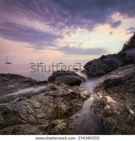Sea landscape with dramatic sky and boats on horizon - stock photo