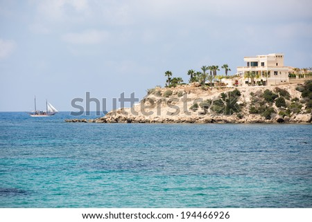 sea landscape with sailboat and villa on the beach