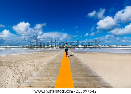 Sea landscape with sportive girl running to the sea. Selective focus - stock photo