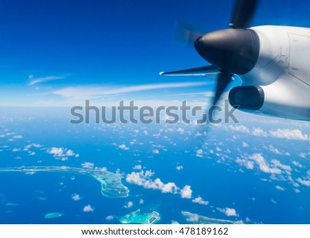 Sea plane flying above Maldives islands. Bird eye view of atolls from Maldives, aerial photography.