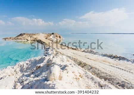 sea postcard of Dead Sea coastline. Road into the  sea. Dead sea road made of Dead sea salt. Sea view. Dead sea landscape. Dead sea postcard. Salt road to the Dead sea. Sea road in Dead sea, Israel. - stock photo