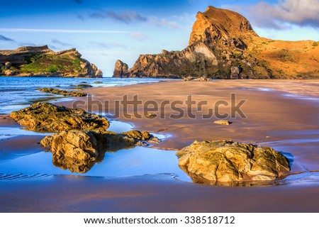 sea, rocks and hills landscape, location - Castlepoint lighthouse, North Island, New Zealand - stock photo