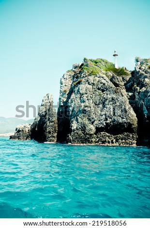 Sea, rocks and small lighthouse, Greece - stock photo