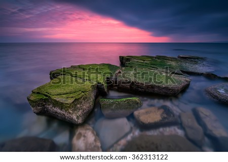 Sea rocks at sunset. Magnificent sunset view in the blue hour at the Black sea coast, Bulgaria. - stock photo