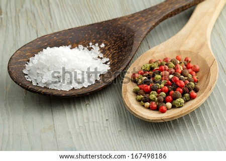 sea salt and mix of peppercorns in wooden spoons - stock photo