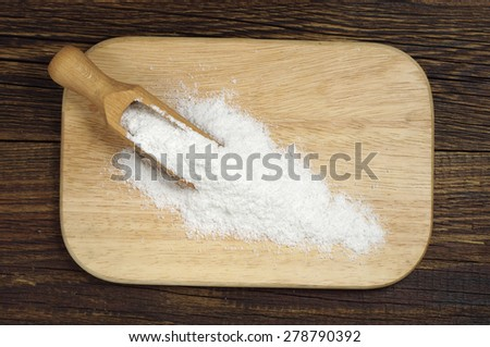 Sea salt and wooden scoop for cooking on cutting board, top view