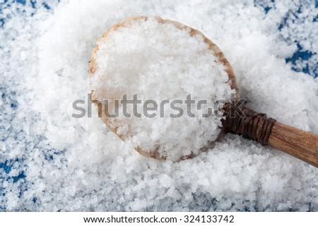 Sea salt ( flower of salt / fleur de sel ) in a spoon from seashell. Top view. - stock photo
