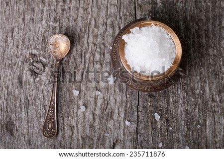 sea salt in an old utensils and a small spoon on a wooden table - stock photo