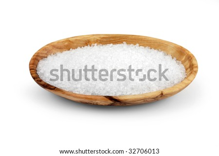 Sea salt in an olive wood oval bowl, over  white background.