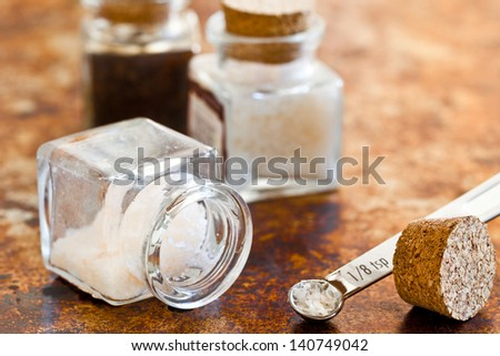 Sea salt in glass jars with cork stoppers. Close up view of textures and colors. - stock photo