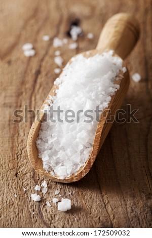 sea salt in wooden scoop  - stock photo