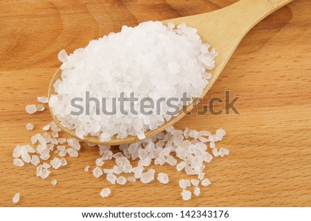 Sea salt in wooden spoon close up - stock photo