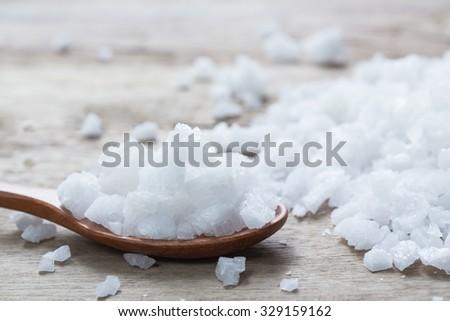 Sea salt in wooden spoon on a wood table. spa salt - stock photo