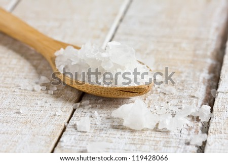 Sea salt in wooden spoon on white  wooden background. Selective focus. - stock photo