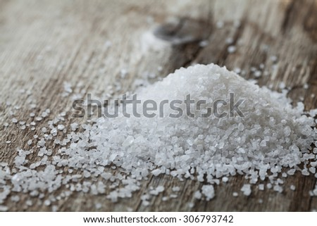 Sea salt on rustic wooden background - stock photo