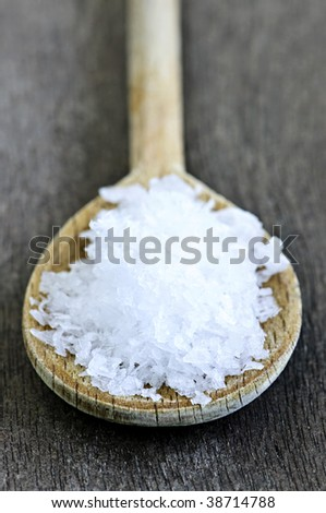 Sea salt on wooden spoon over wooden table background - stock photo